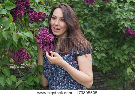 Beautiful woman in garden among the lilacs. People