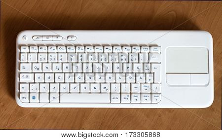 white keyboard lies on brown wood texture