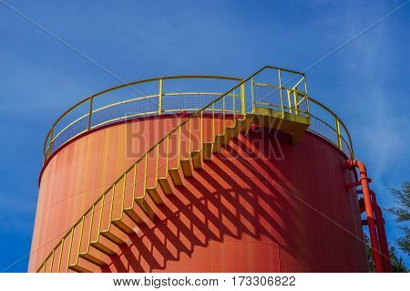 Red tanks in tank oil depot with iron staircase