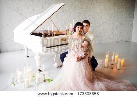 father mother and young daughter near a piano. in the background a white brick wall