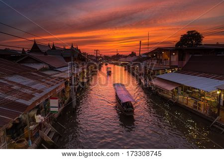 Sunset and Boat on canal with old market this lace is call Ampawa floating market SamuthsongkramThailand