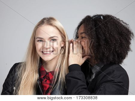 Two teenage hipster girls in studio. One says the other some horrifying secret. Isolated on white background.