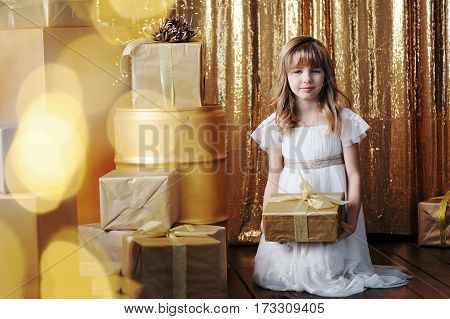 Young girl in white tender dress with gold gift boxes on birthday, with golden background