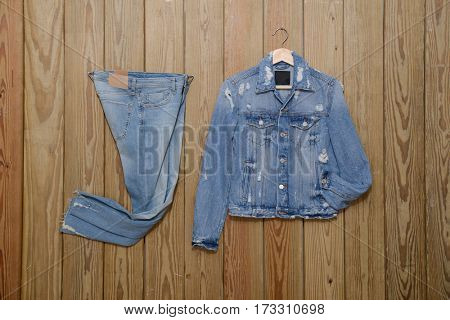 Jeans jacket with Blue jeans trousers - wooden background