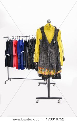 Variety of casual female clothes of different colors on hangers