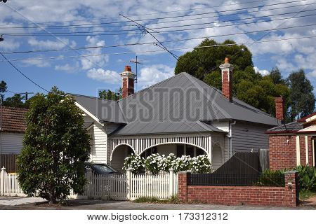 suburban house on sunny day with grey roof and white picket fence
