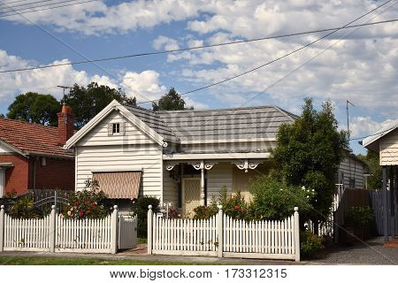 quaint wooden panelled house with white picket fence on sunny day in suburbia