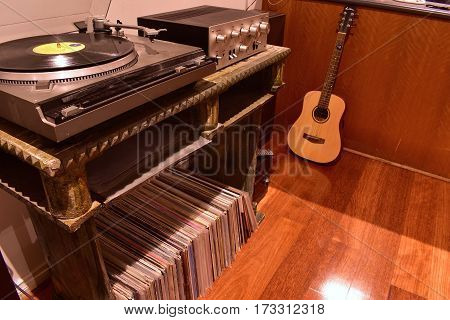 vintage record player with records in foreground and guitar in background