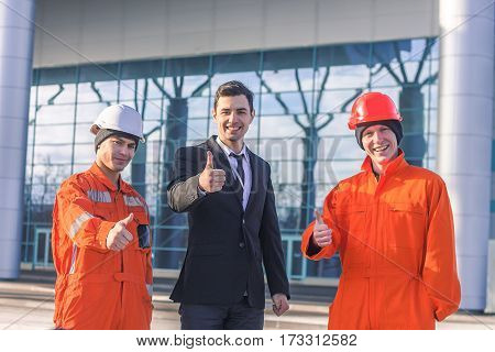 Smiling manager and the builders gesturing thumb up. Horizontal outdoors shot.