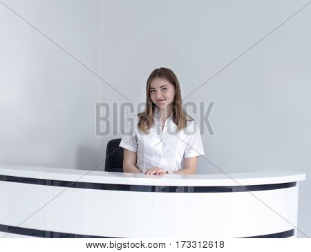 Young receptionist at hospital or medical clinic waiting for patient. White background