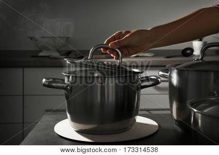 Preparing food in metal pan in kitchen
