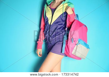 Fashion concept. Young woman with colourful backpack on blue background, closeup