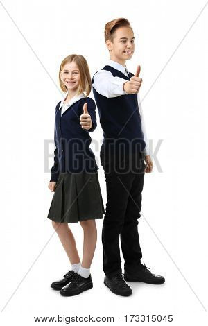 Cute girl and boy in school uniform showing thumb up gesture on white background
