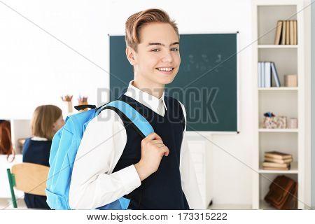 Teenage boy in school uniform standing in classroom