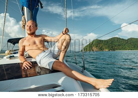 Portrait of a bearded young man with a red mustache lying on the deck of a sailing boat during a walk on the sea. Sunbathe on the deck. Luxury travel