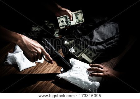 Drug trafficker holding a lot of cash on hand and use gun pushing drugs to the customer in the Drug dealing concept about the drug problem