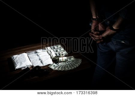 selective focus at drug and money on table when drug dealer was arrested in handcuffs with concept about the drug problem