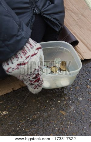Coins of street beggar - hand in mitten holds conteiner with russian rubles, winter cold russia, telephoto