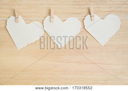 Three paper hearts hang on light wooden background