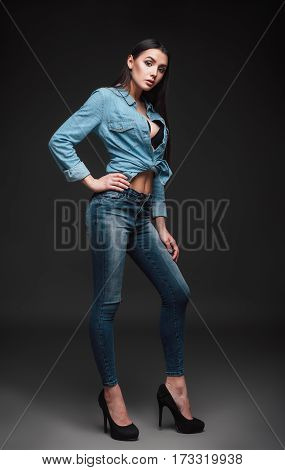 Studio fashion shot: portrait of a beautiful young woman in jeans and shirt
