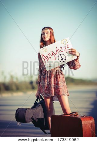 Beautiful young hippie girl hitchhiking on the road at sunset time.