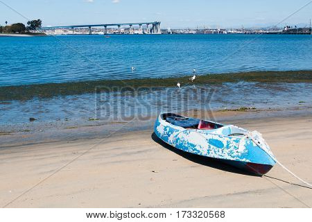 Glorietta Marina Park beach in Coronado, California, with a kayak in the foreground and the San Diego-Coronado Bay Bridge and San Diego Bay in the background.
