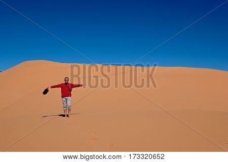 Man hiking in desert. Coral Pink Sand Dunes State Park. Cedar City. Kanab. Utah. United States.
