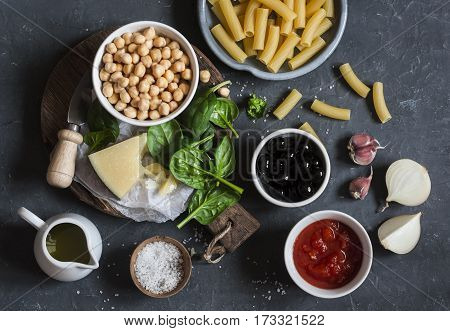 Ingredients for cooking rigatoni pasta with chickpeas spinach and olives in a tomato sauce on a dark background top view. Vegetarian food concept