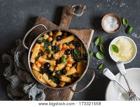 Rigatoni pasta with chickpeas spinach and olives in a tomato sauce on a dark background top view. Vegetarian food concept