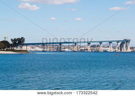 The San Diego-Coronado Bay Bridge spanning San Diego Bay, with a nearby sailboat.