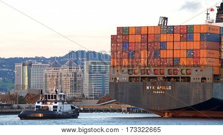 Oakland CA - February 22 2017: Tugboat AHBRA FRANCO at the stern of NYK APOLLO assisting the vessel to maneuver into the Port of Oakland. A tugboat maneuvers vessels by pushing or towing them.