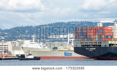 Oakland CA - February 24 2017: Tugboat REVOLUTION at the stern of cargo ship NYK AQUARIUS assisting the vessel to maneuver into the Port of Oakland the fifth busiest port in the U.S.