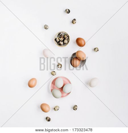 White and brown Easter eggs and quail eggs on white background. Flat lay top view. Traditional spring concept.