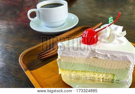 Vanilla cake placed on a wooden plate with a cup of coffee.