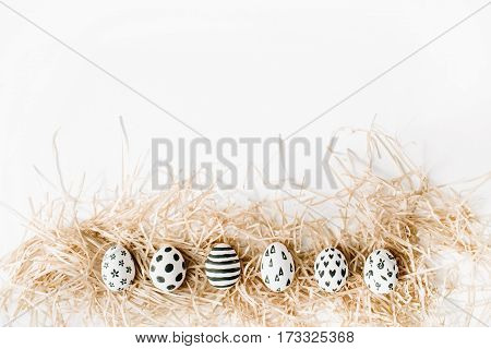 Fancy Easter eggs in nest on white background. Flat lay top view. Traditional spring concept.