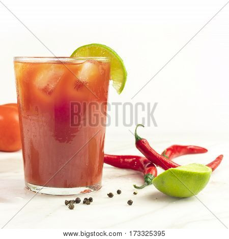 A square photo of a Bloody Mary cocktail with red hot chili peppers, slices of lime, tomatoes, and copyspace