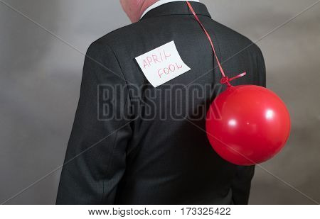 Fool's day is businessman with a balloon behind his back.