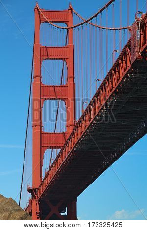 South tower and roadway of the Golden Gate Bridge, San Francisco, as viewed from beneath, orange-red against a blue sky.