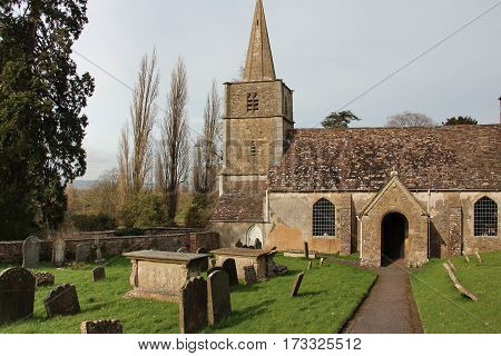 Old English country church with steeple, graveyard and porch entrance.