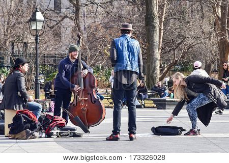 8 February 2017 - New York City NY: Unidentified woman making a donation for musicians that were playing at Washington Square.