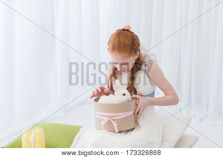 Beautiful red-haired girl child presented a rabbit in a gift box.