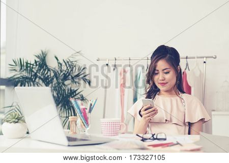 Pretty Asian female tailor reading message in her smartphone
