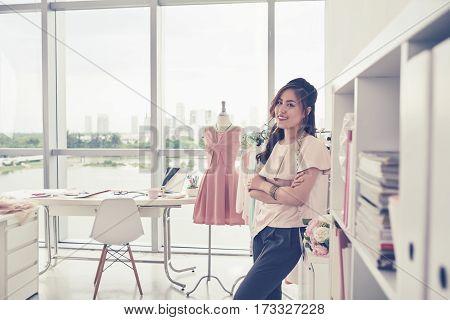 Beautiful Vietnamese fashion designer standing in her studio