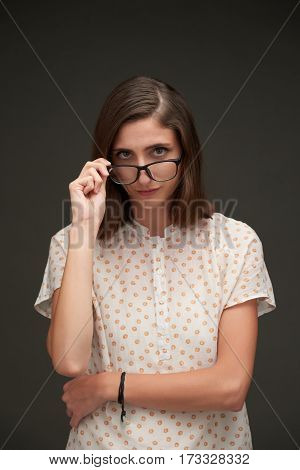 Portrait of young woman looking over her glasses