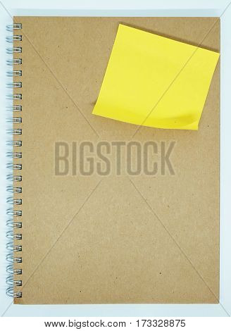 Yellow sticky note on notebook , clean notebook