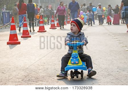 KOLKATA WEST BENGAL INDIA - JANUARY 17TH 2016 : Little boy riding a bicycle in an road made empty for children to play around wondering look at Kolkata.