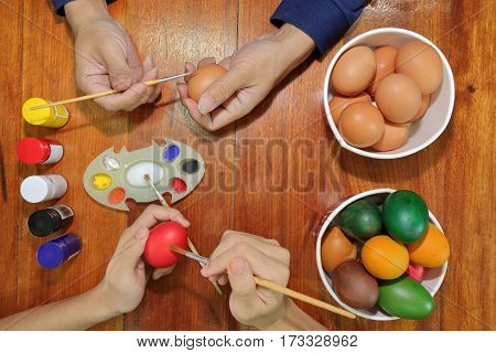 Top view of hands of young people painting easter eggs with a paintbrush and palette on wooden top.