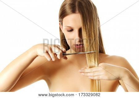 Attractive young woman is cutting her long natural hair.