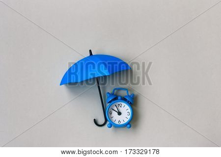 Blue alarm clock under an umbrella on a gray background concept of protection time