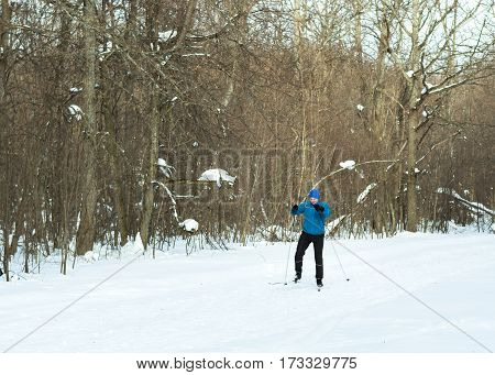 The man on the crosscountry skiing in winter forest. Ice ridge course skiing. Healthy lifestyle concept.